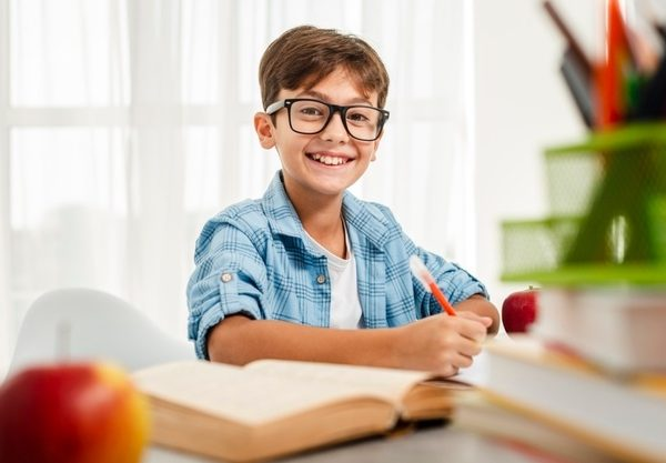 high-angle-smiley-boy-with-glasses-studying_23-2148355253